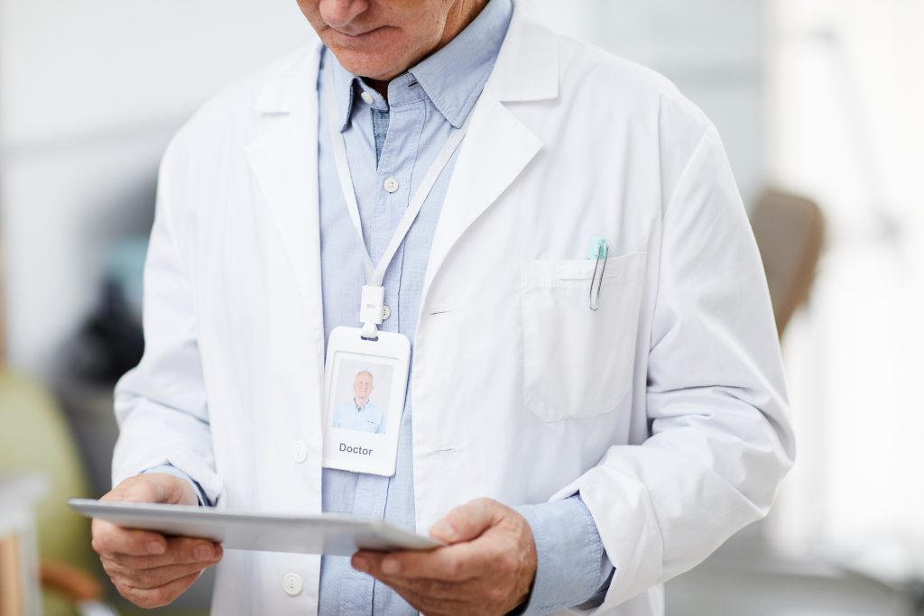 Senior Doctor using Tablet